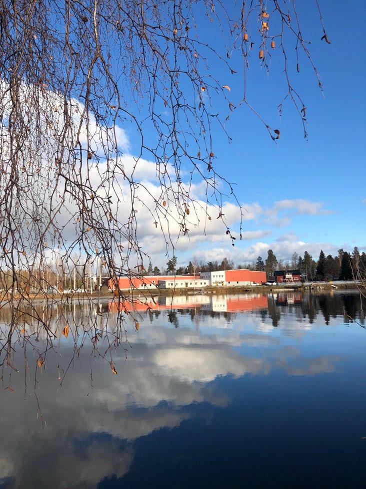 Bild på sjö med byggnad bakom som speglar sig i vattnet